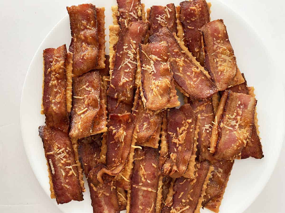 Twenty bacon crackers with Parmesan cheese stacked on a plate for serving.