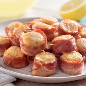 bacon wrapped scallops piled on a plate with lemon in the background