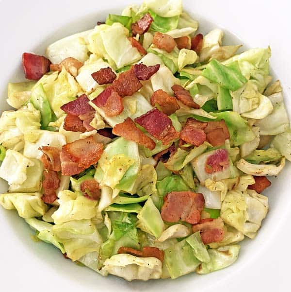 A white dish with fried cabbage and bacon