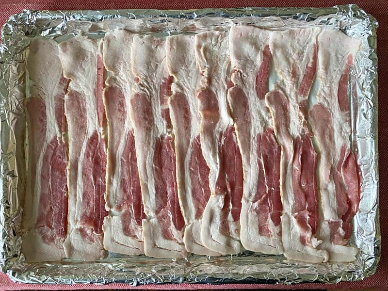 9 strips of bacon arranged in a foil and parchment paper lined baking pan.