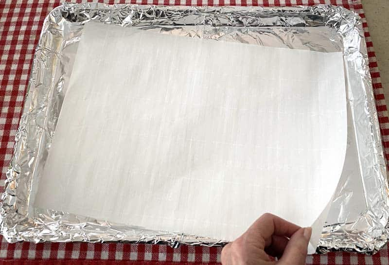 A hand laying a sheet of white parchment paper over a baking sheet lined with foil.