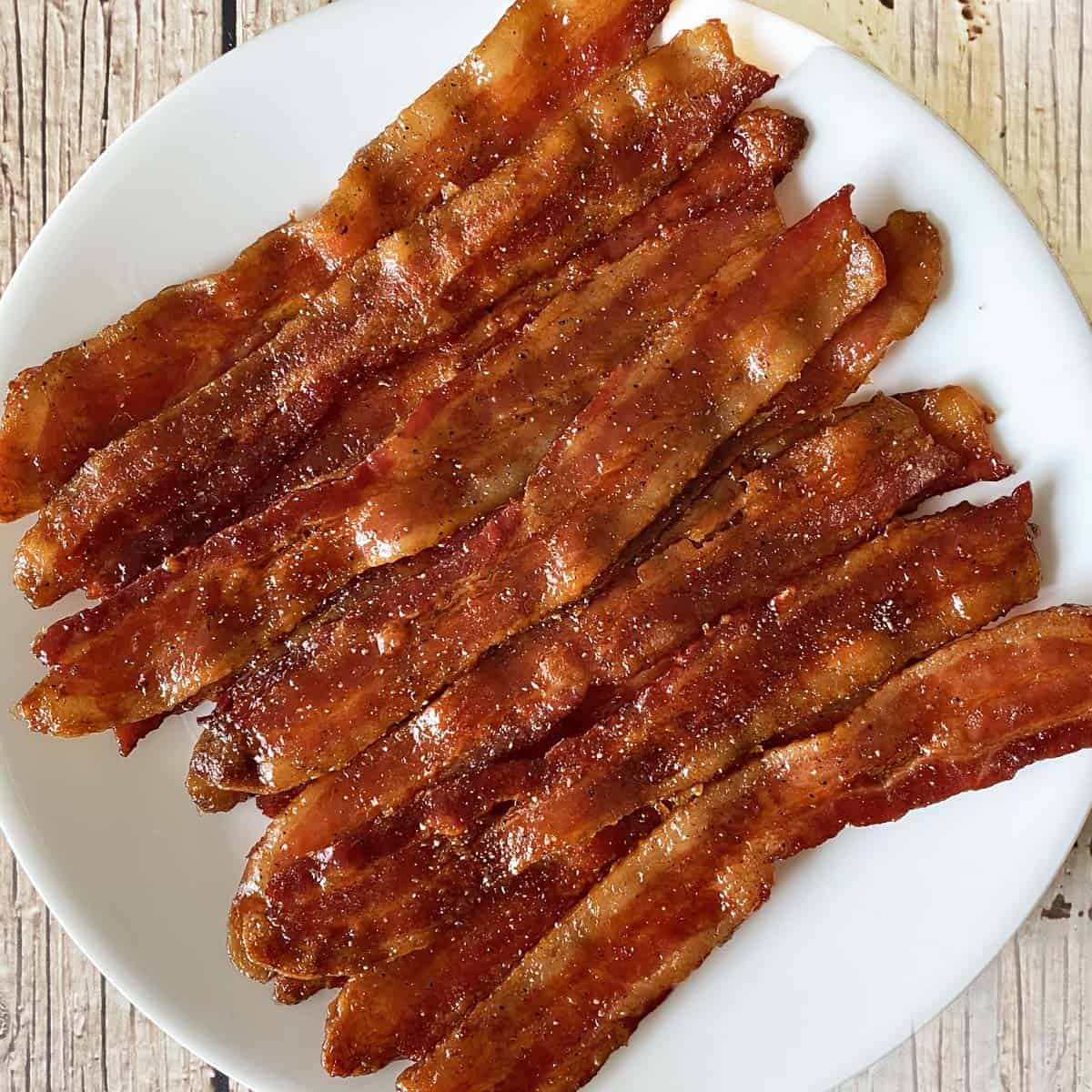 maple candied bacon on a white plate against a weathered wood background
