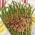Asparagus spears on a white platter, topped with crumbled bacon, bread crumbs and Parmesan cheese, garnished with six lemon wedges.