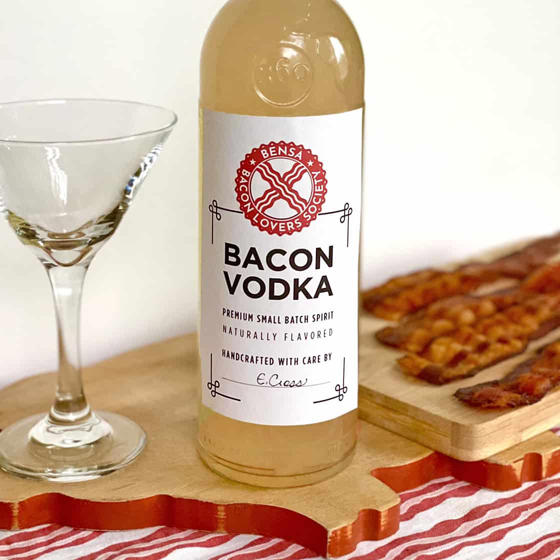 From left, a martini glass, a bottle of bacon vodka and four cooked bacon strips, on wooden cutting boards