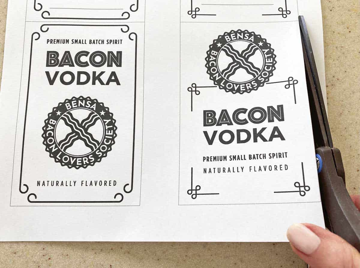 A hand show with a pair of scissors, cutting a sheet of bacon vodka labels