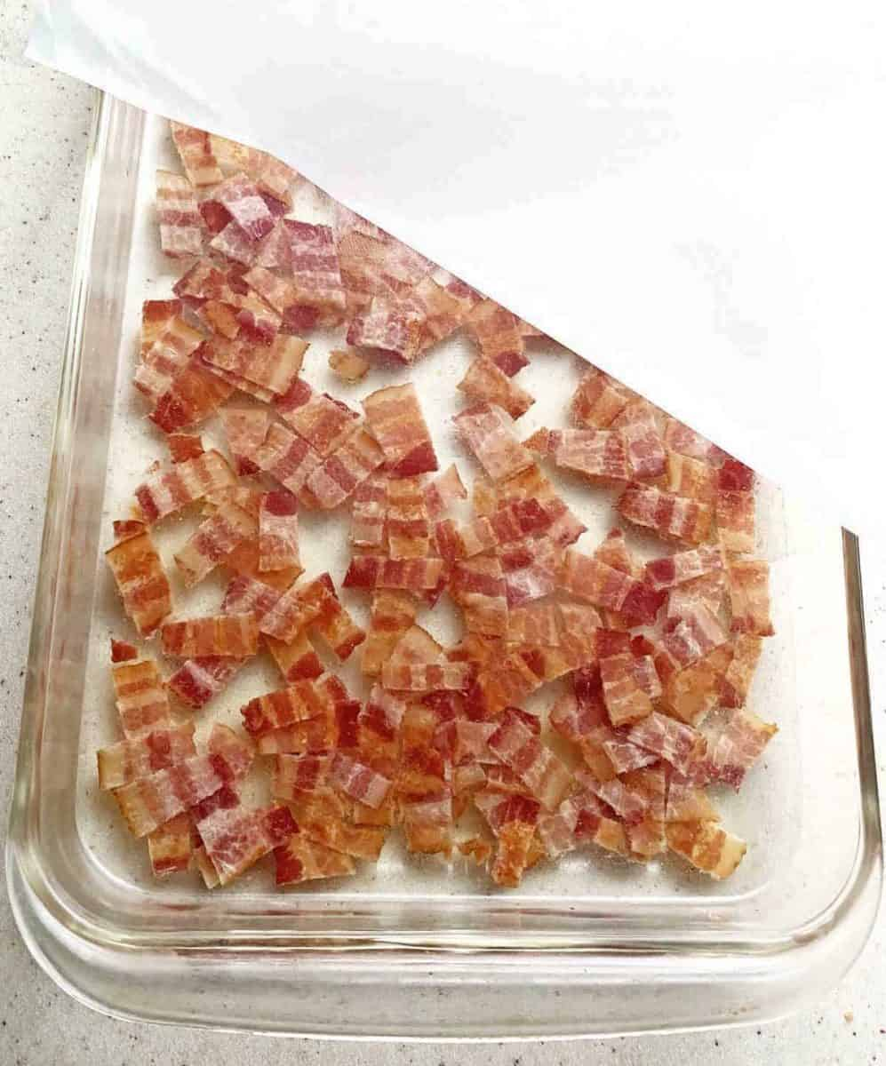 Putting plastic wrap over the bacon vodka mixture in a dish, before refrigerating.