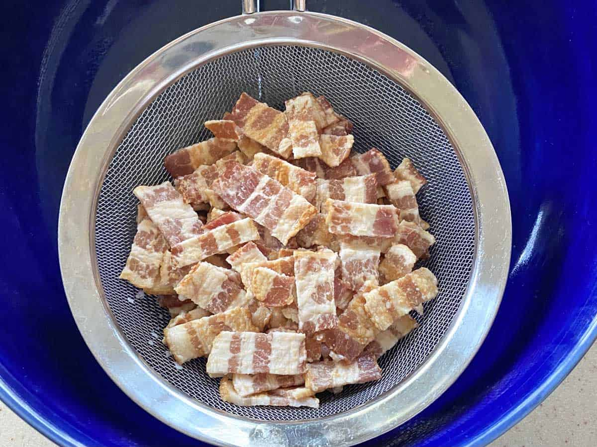 A strainer over a blue bowl with the bacon pieces (they look weird and pale) being strained out.