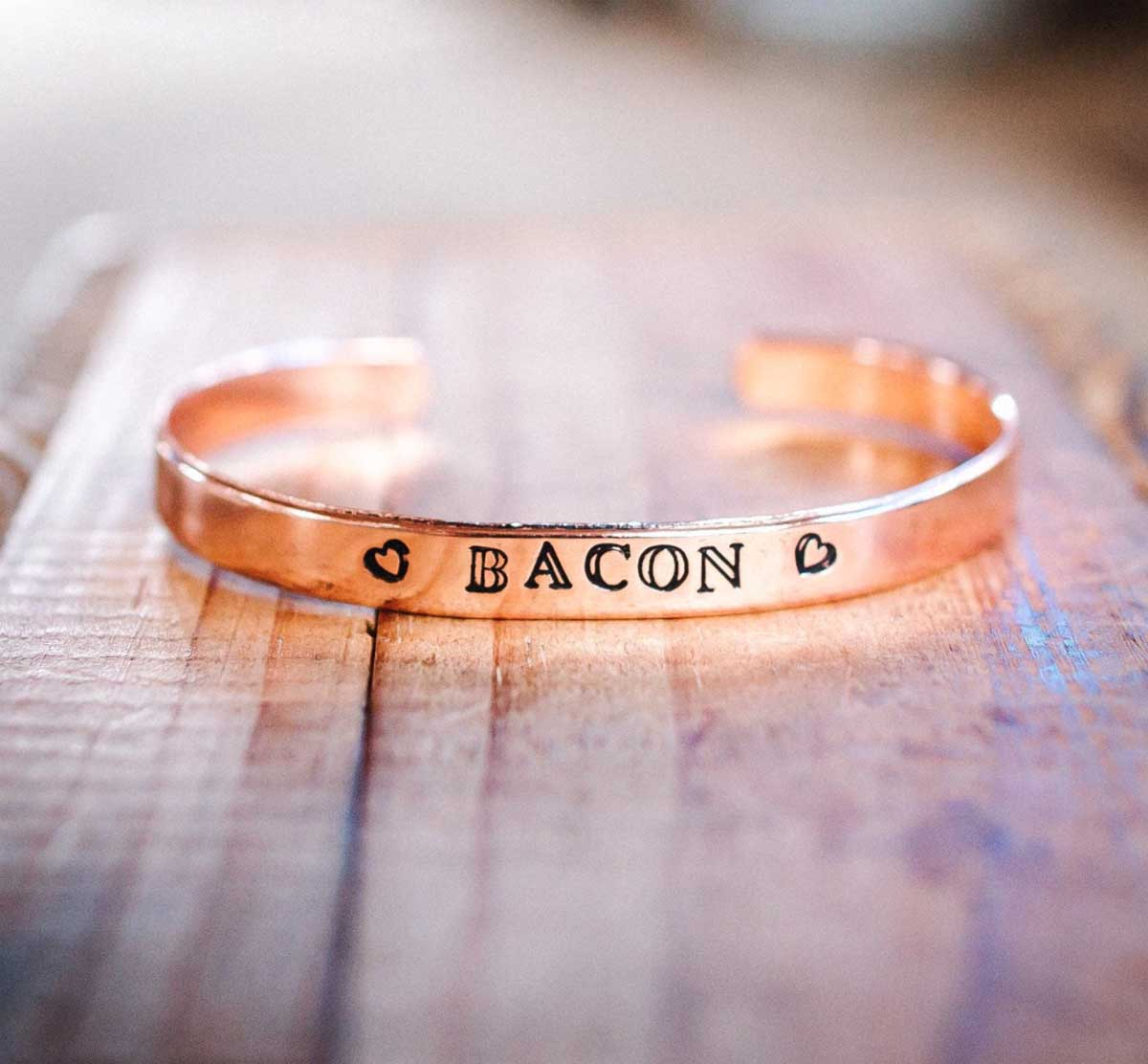 """A copper bracelet with the word """"BACON"""" hand stamped across the front."""